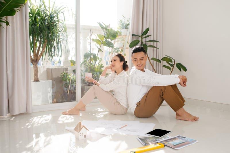 Aziatisch echtpaar op de vloer met planning voor het versieren van een blauwdruk plan Huisvesting gewoon getrouwd diversiteit int royalty-vrije stock foto's
