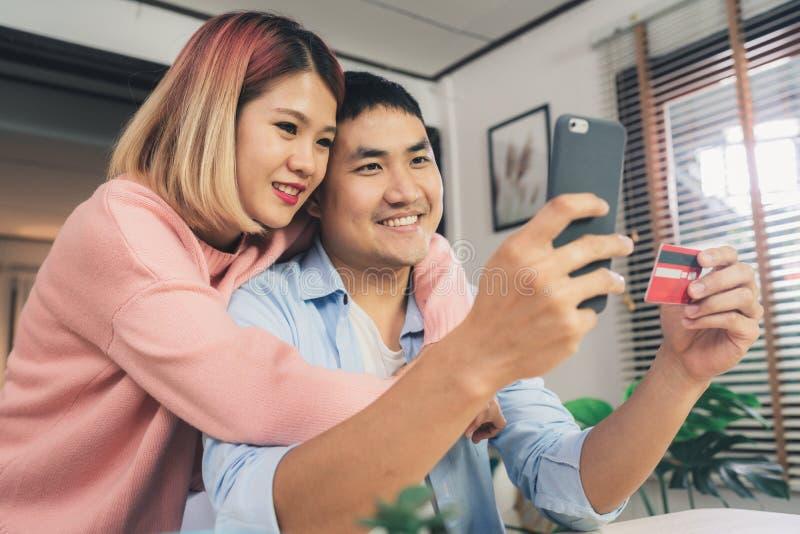 Aziatisch familiepaar die smartphone gebruiken die nieuws bespreken of het online het winkelen thuis zitten samen op bureau doen royalty-vrije stock foto's