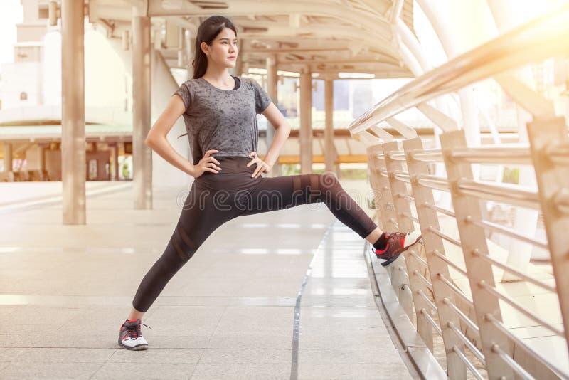 Aziatisch geschiktheids jong vrouw het uitrekken zich been op een training die van de spoorbrug op straat in stedelijke stad uito royalty-vrije stock foto