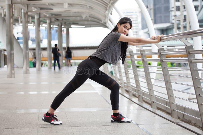 Aziatisch geschiktheids jong vrouw het uitrekken zich been op een training die van de spoorbrug op straat in stedelijke stad uito royalty-vrije stock foto's