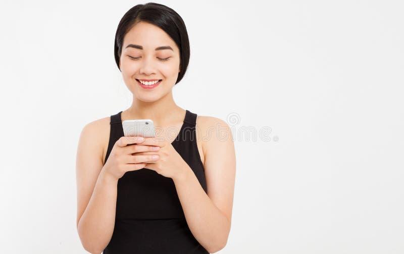 Aziatisch glimlachmeisje die cellphone gebruiken die op witte achtergrond wordt geïsoleerd stock fotografie