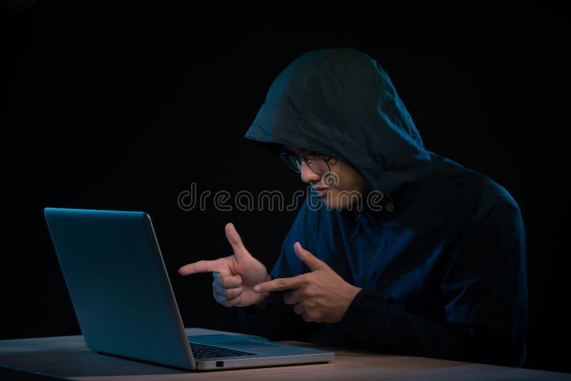 Aziatisch hakker het binnendringen in een beveiligd computersysteem computernetwerk met laptop in dark Cyber stock afbeelding