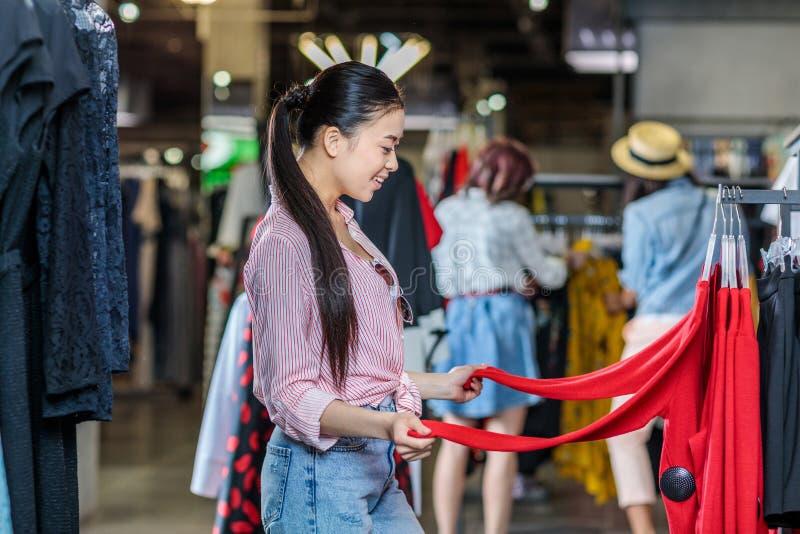 Aziatisch hipstermeisje die kleren in winkelcomplex kiezen stock foto