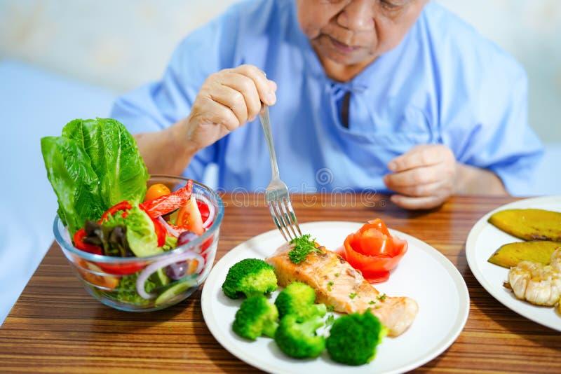 Aziatisch hoger of bejaard oud damevrouw geduldig het eten ontbijt gezond voedsel met hoop en gelukkig terwijl het zitten en hong stock afbeeldingen