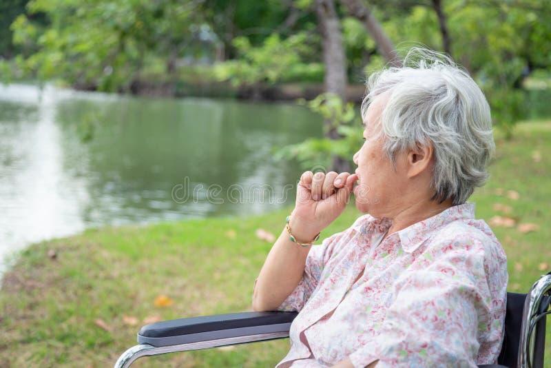 Aziatisch hoger beklemtoond vrouwengevoel, de ongerust gemaakte vrouwelijke spijkers van de betenvinger in rolstoel openluchtpark stock foto's