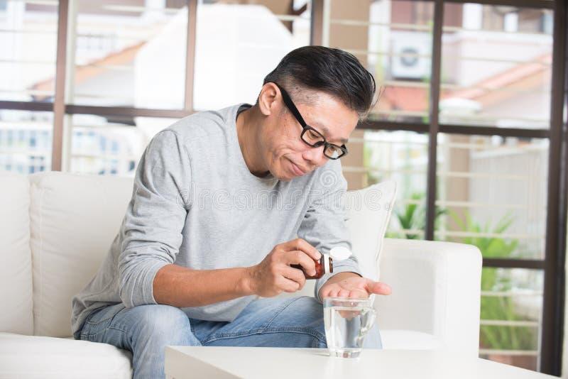 Aziatisch hoger mannetje die pillen nemen stock fotografie
