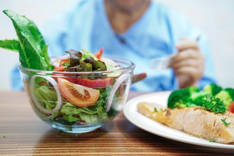 Aziatisch hoger oud damevrouw geduldig het eten het ontbijt gezond voedsel van de saladegroente in het ziekenhuis royalty-vrije stock afbeeldingen