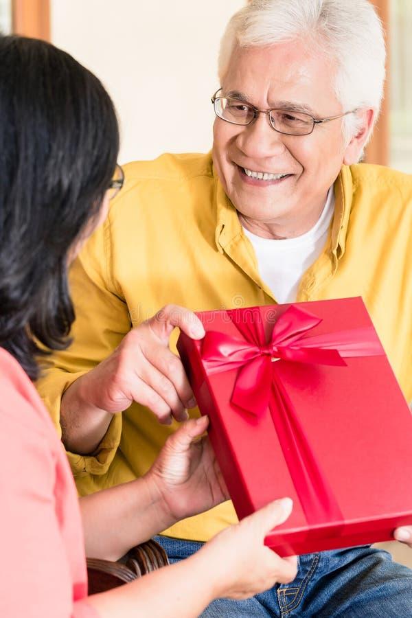 Aziatisch hoger paar die in liefde terwijl het houden van gift glimlachen stock foto