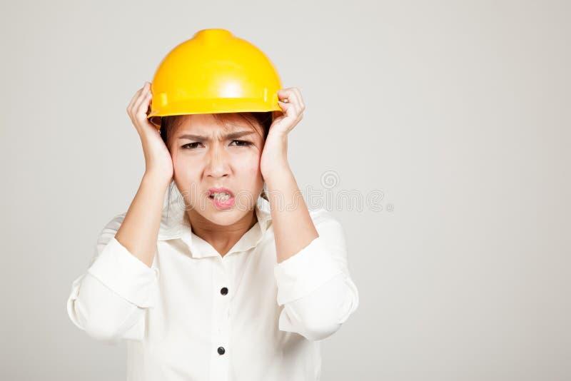 Aziatisch Ingenieursmeisje met bouwvakker geworden hoofdpijn stock foto's