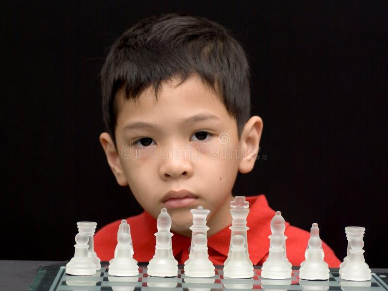 Aziatisch jong geitje het spelen schaak stock afbeelding