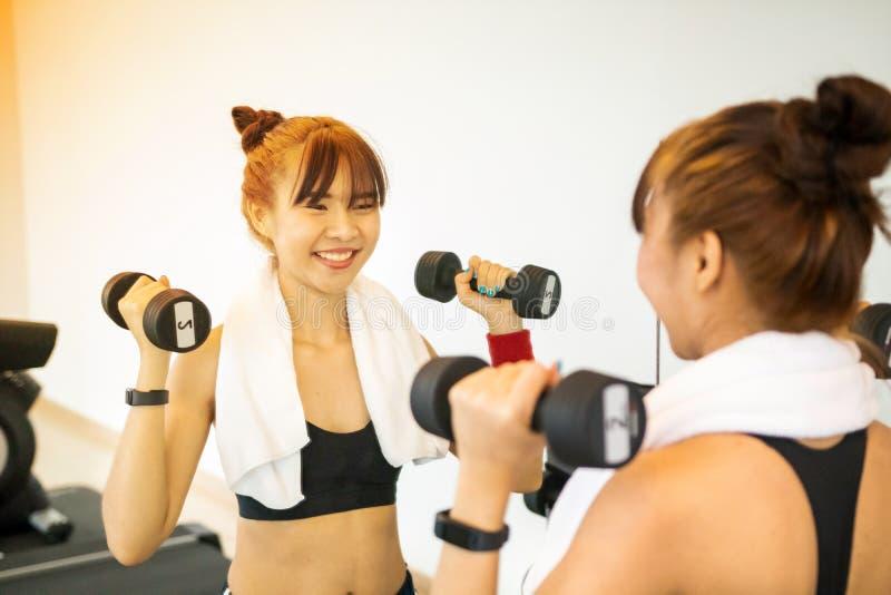 Aziatisch jong meisje die exrecises met domoor in gymnastiek doen, die haar lichaam door spiegel ochtend bekijken royalty-vrije stock afbeeldingen