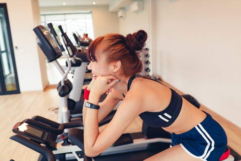 Aziatisch jong meisje die exrecises met domoor in gymnastiek doen, die haar lichaam door spiegel ochtend bekijken royalty-vrije stock foto's
