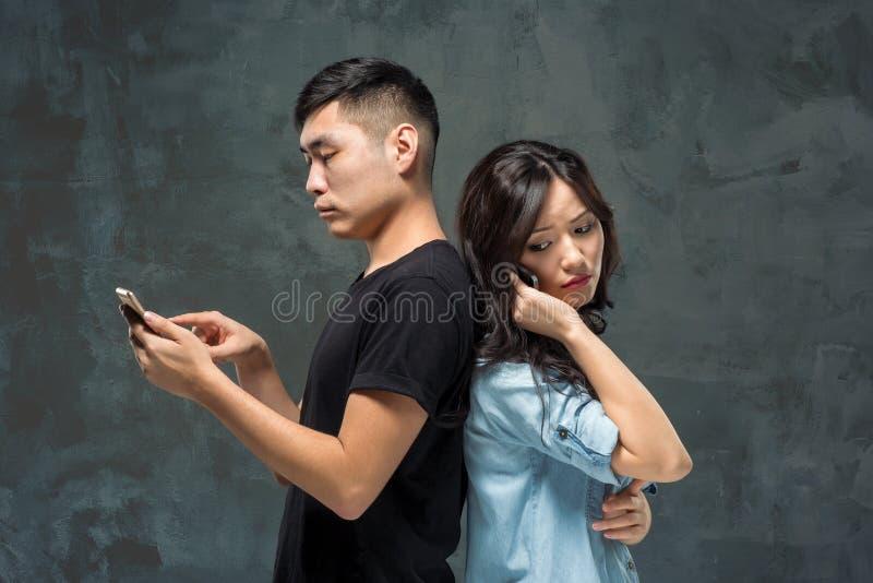 Aziatisch jong paar die cellphone, close-upportret gebruiken stock afbeelding