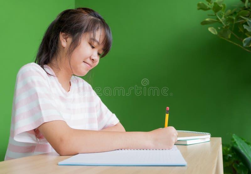 Aziatisch jong tienermeisje het schrijven thuiswerk bij het lusje van de schoolbibliotheek royalty-vrije stock afbeelding