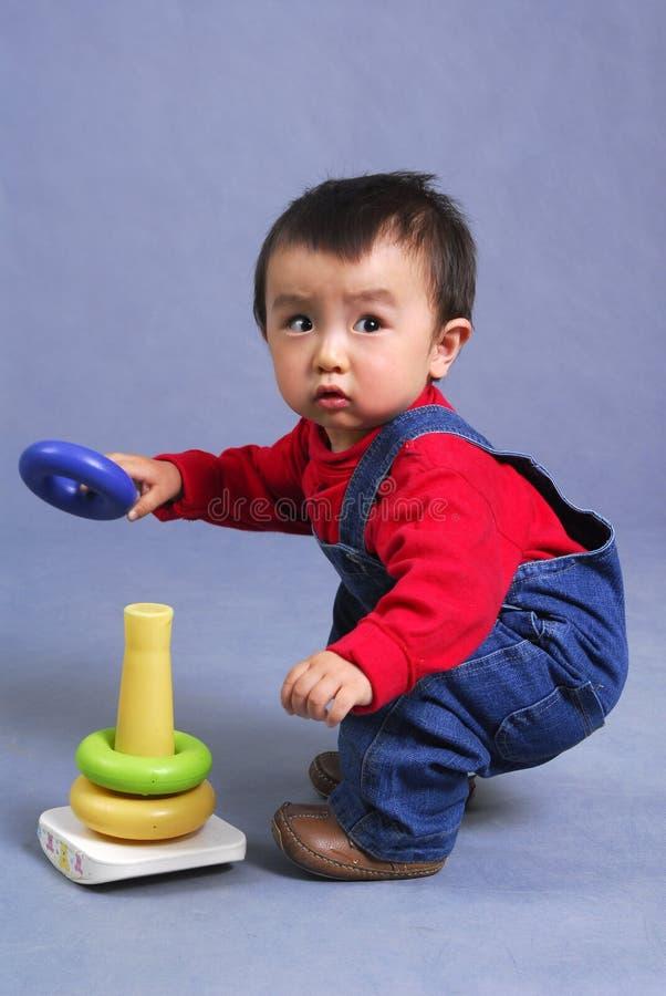 Aziatisch jongen het spelen stuk speelgoed stock foto's