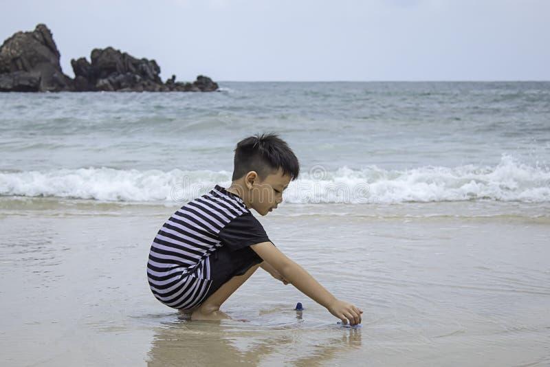 Aziatisch jongen het spelen stuk speelgoed op een overzees strand royalty-vrije stock afbeeldingen