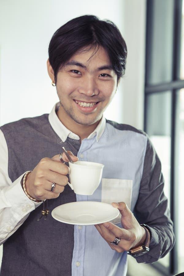 Aziatisch jongere mens toothy het glimlachen gezicht met hete koffiekop in han royalty-vrije stock foto's