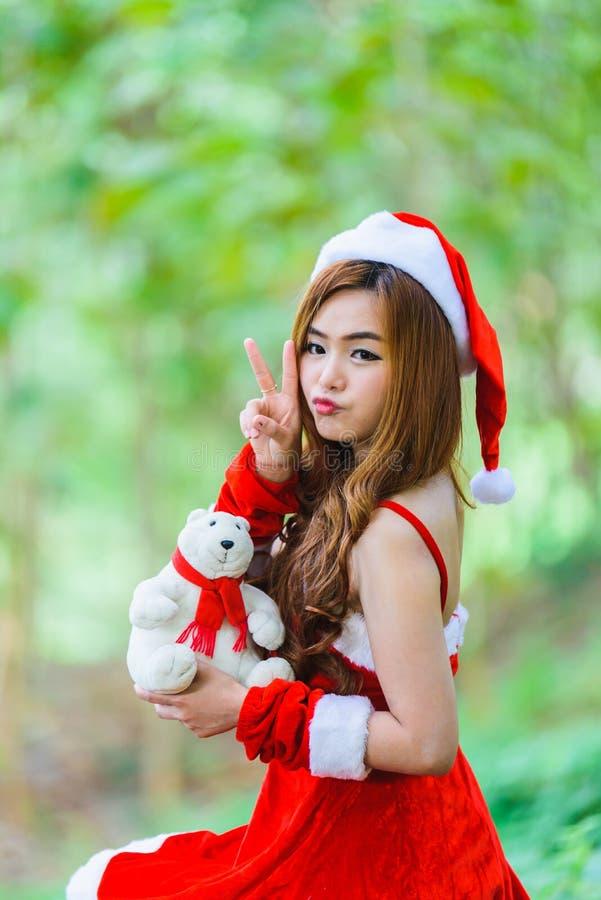Aziatisch Kerstmanmeisje met beer stock foto's
