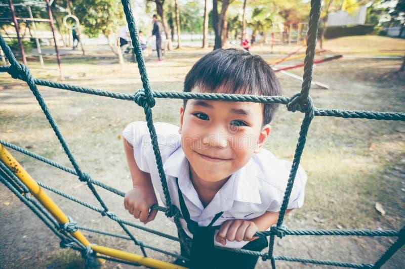 Aziatisch kind die in een kabel bij kinderenspeelplaats beklimmen Uitstekend t stock fotografie