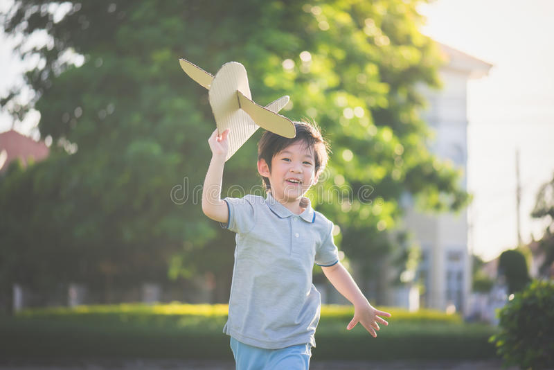Aziatisch kind het spelen kartonvliegtuig stock foto