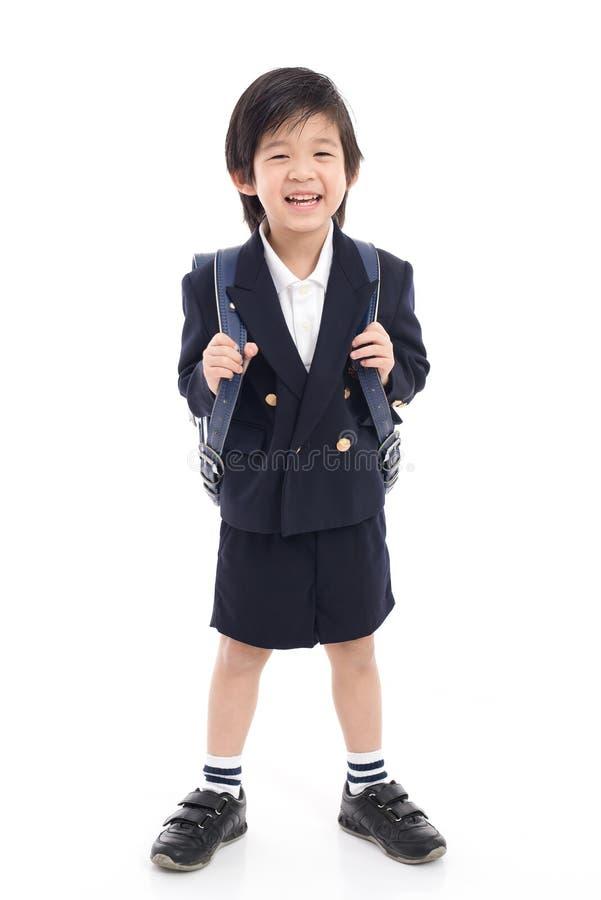 Aziatisch kind in school eenvormig met blauwe schooltas royalty-vrije stock afbeeldingen