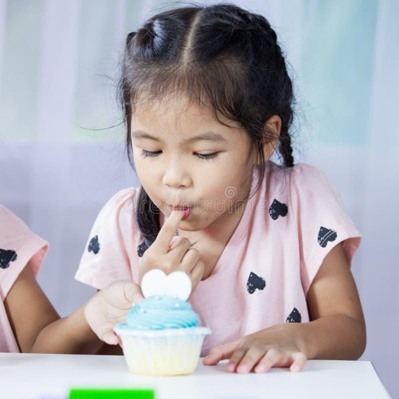 Aziatisch kindmeisje die heerlijke blauwe cupcake eten stock afbeeldingen