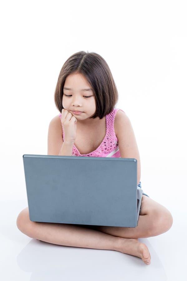 Aziatisch kindmeisje die laptop en het denken gebruiken stock afbeeldingen