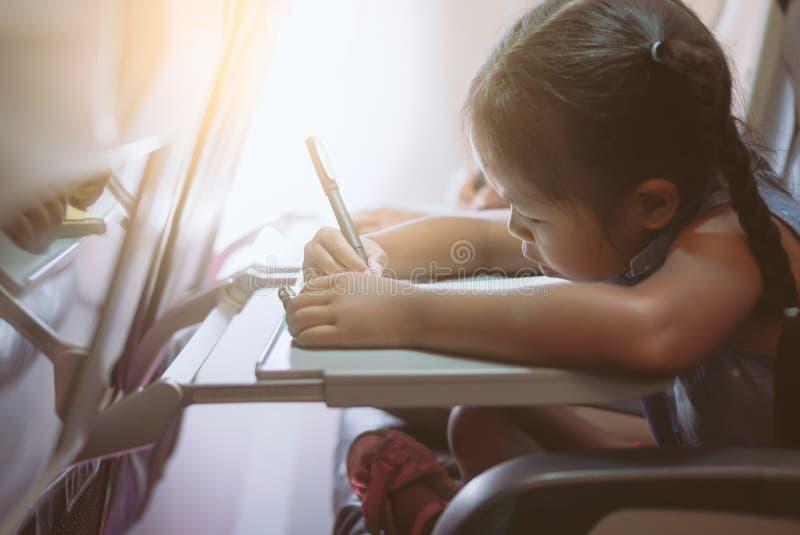 Aziatisch kindmeisje die tegen een vliegtuig en het besteden tijd door te trekken reizen en het lezen van een boek tijdens de vlu royalty-vrije stock fotografie