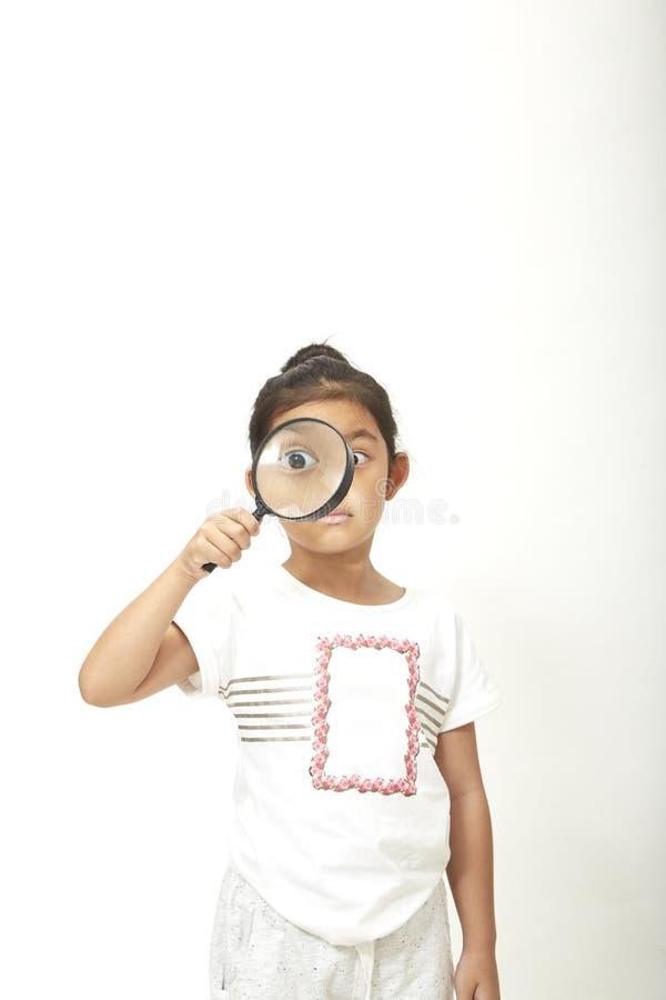 Aziatisch kindmeisje met een vergrootglas royalty-vrije stock foto's