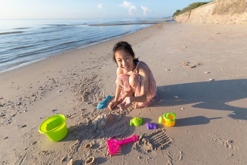 Aziatisch leuk meisje het spelen zand op het strand, de de zomervakantie en r stock fotografie