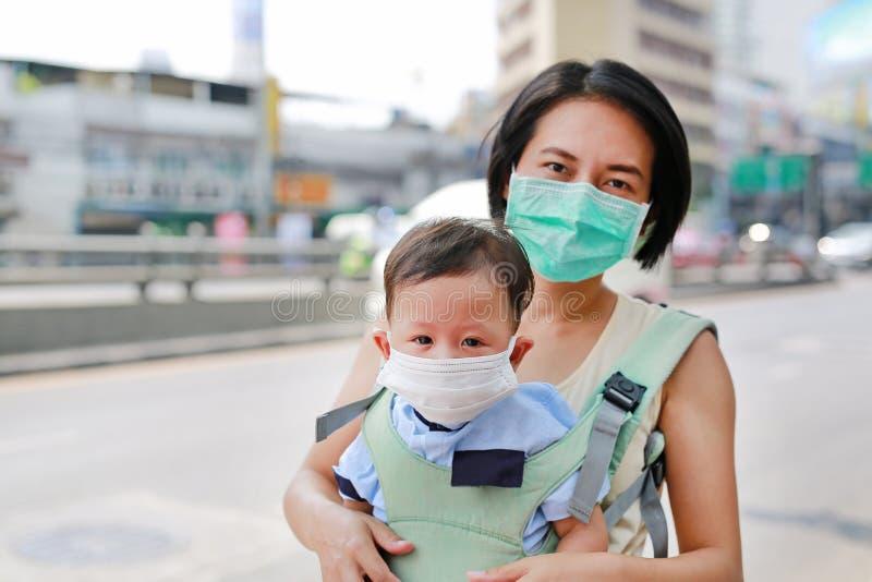 Aziatisch mamma die haar baby vervoeren die door hipseat met het dragen van een beschermingsmasker tegen luchtvervuiling in de st stock afbeelding