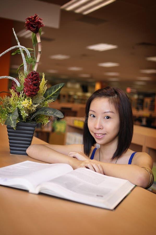 Aziatisch meisje in bibliotheek stock foto's