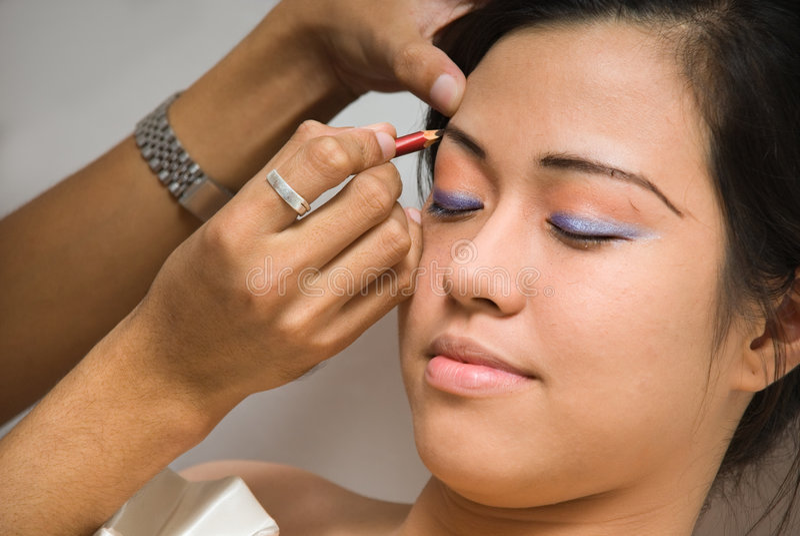 Aziatisch meisje dat eyelinersamenstelling ontvangt royalty-vrije stock afbeeldingen