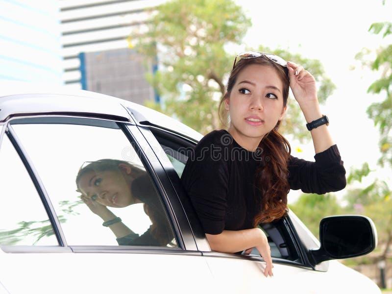 Aziatisch meisje dat rug van auto bekijkt royalty-vrije stock foto's