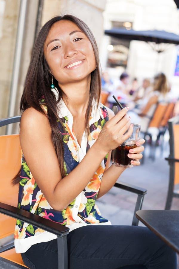 Aziatisch meisje dat van een soda op terras geniet royalty-vrije stock fotografie
