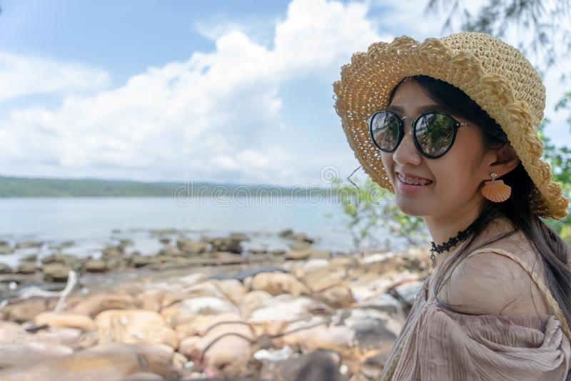 Aziatisch meisje die bij overzees van de de zomersteen strand op tropisch eiland glimlachen stock foto's