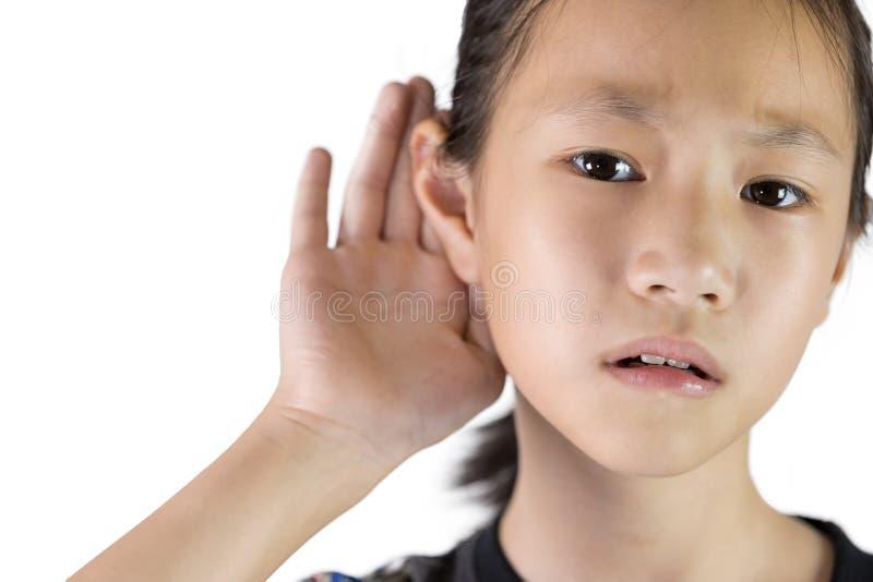 Aziatisch meisje die door hand's tot het oor luisteren royalty-vrije stock foto's
