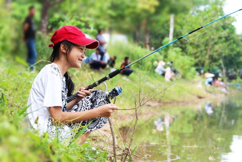 Aziatisch meisje die een hengel door het kanaal of de rivier genieten van te gebruiken stock foto