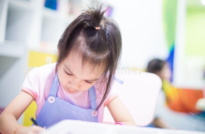 Aziatisch meisje die een schort het leren kunstklaslokaal dragen stock afbeelding