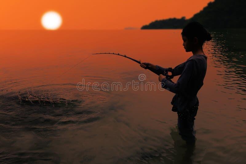 Aziatisch meisje die en zich met staaf en spoel in overzeese nea bevinden vissen stock foto