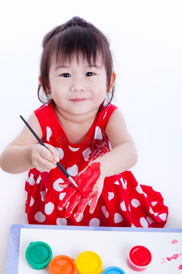 Aziatisch meisje die haar hand schilderen die tekeningsinstrumenten, creativi gebruiken stock afbeelding