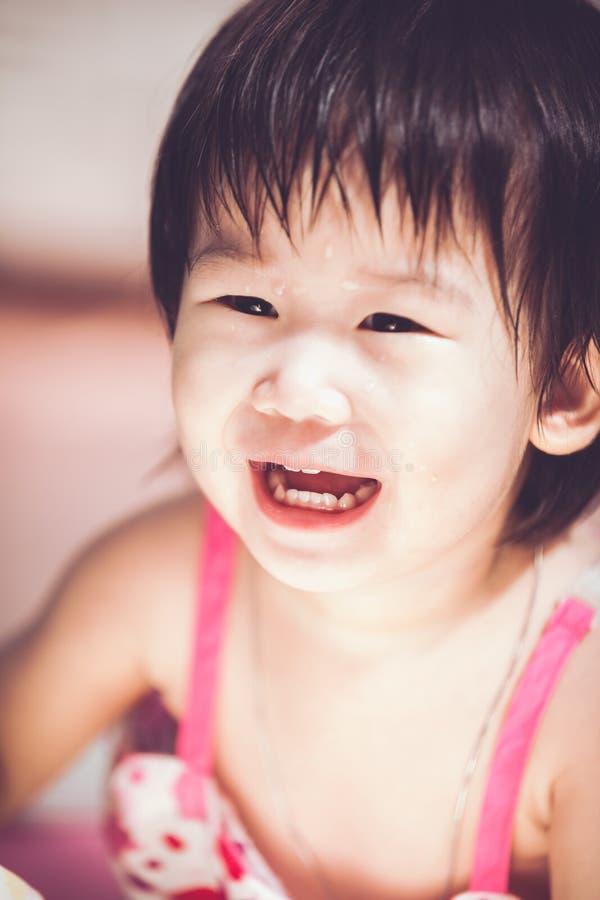 Aziatisch meisje die met perfecte glimlach met daling op haar gezicht glimlachen royalty-vrije stock afbeeldingen