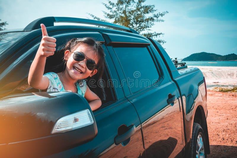 Aziatisch meisje die met perfecte glimlach glimlachen terwijl het zitten in de auto stock foto