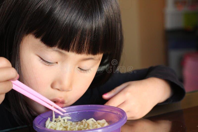 Aziatisch Meisje die Noedels eten stock afbeelding
