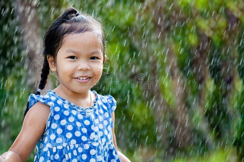 Aziatisch meisje die pret met de regen hebben te spelen royalty-vrije stock foto's