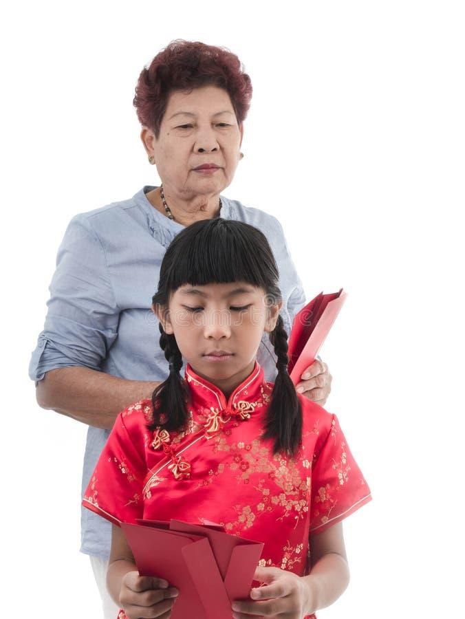 Aziatisch meisje die in Rode Chinese kleding met haar grootmoeder beklemtonen stock fotografie