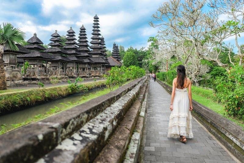 Aziatisch meisje die zich voor van de poort van Pura Taman Ayun Temple in Bali, Indonesië bevinden stock foto