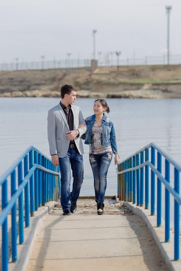Aziatisch meisje en Europese kerel die langs pijler lopen royalty-vrije stock foto