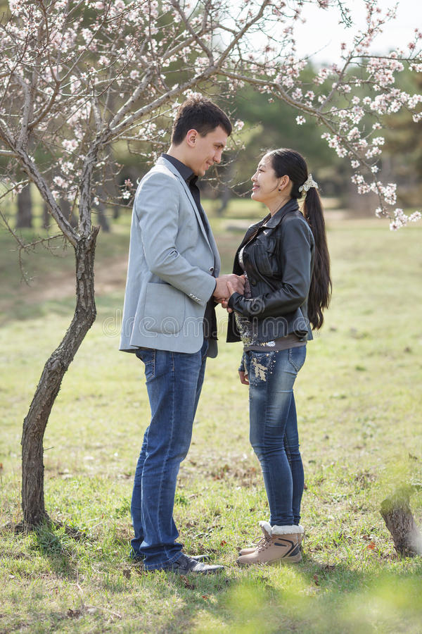 Aziatisch meisje en Europese kerel die zich tegen van het tot bloei komen bevinden almon stock afbeelding