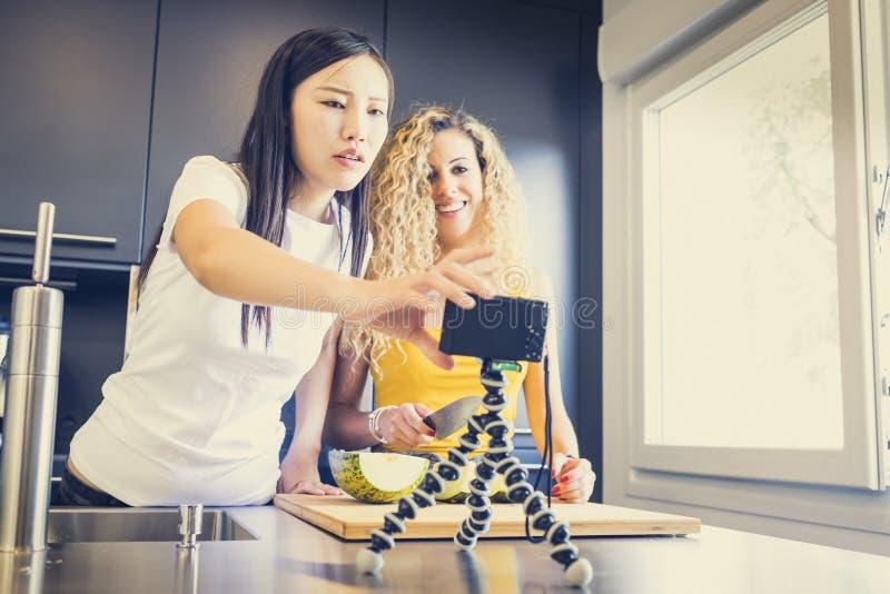 Aziatisch meisje en Kaukasisch meisje die een video voor een blog met fruit in de keuken maken stock fotografie